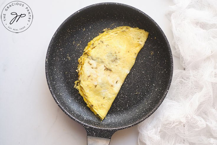 The cooked egg in the pan, folded in half to form the omelet.