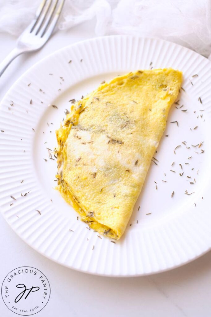 And up close shot of the One Egg Omelet on a white plate, sprinkled with dried herbs. A fork rests on the table to the top left of the shot.