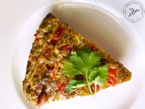 A single slice of the finished Southwestern Crustless Quiche Recipe on a white plate.