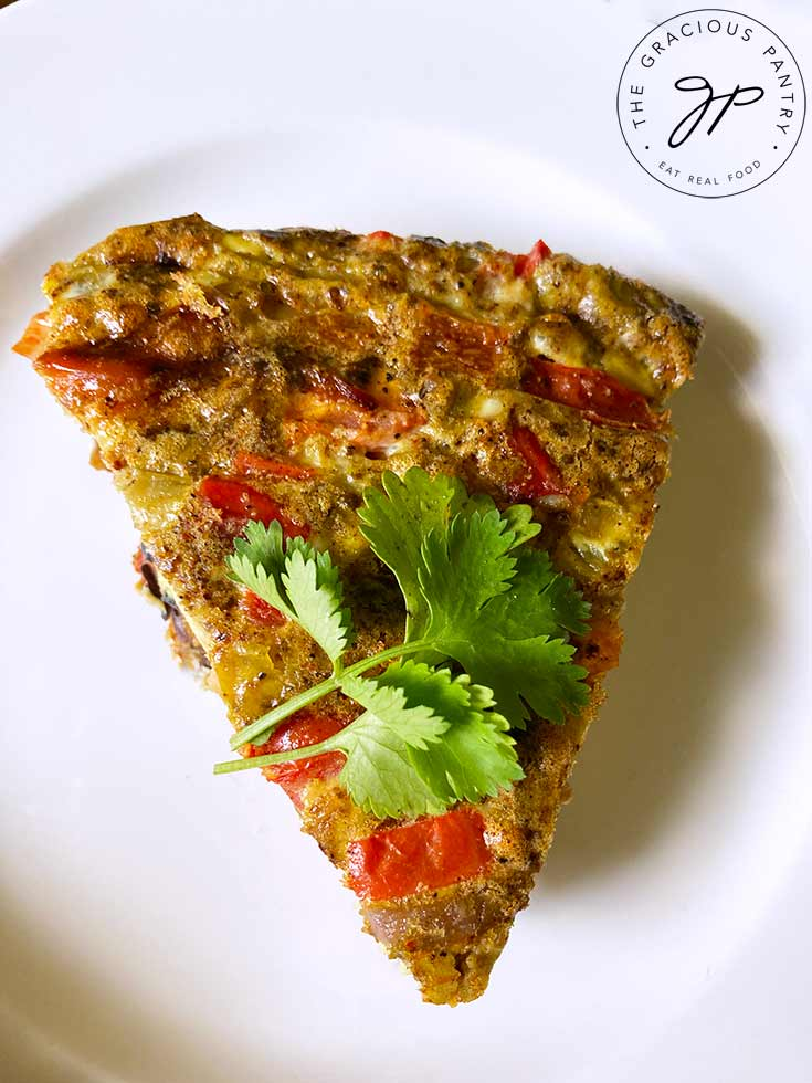 An overhead view looking down onto a single slice of Southwestern Crustless Quiche on a white plate.