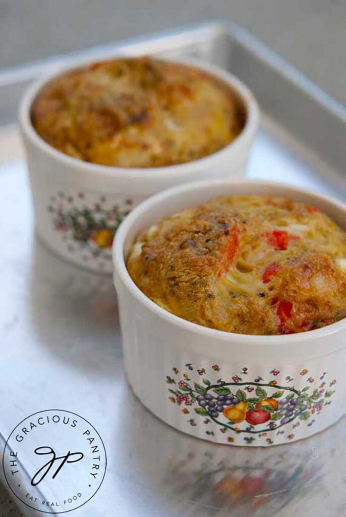 Two small ramekins sit on a cookie sheet with just baked Southwestern Crustless Quiche in each of them.