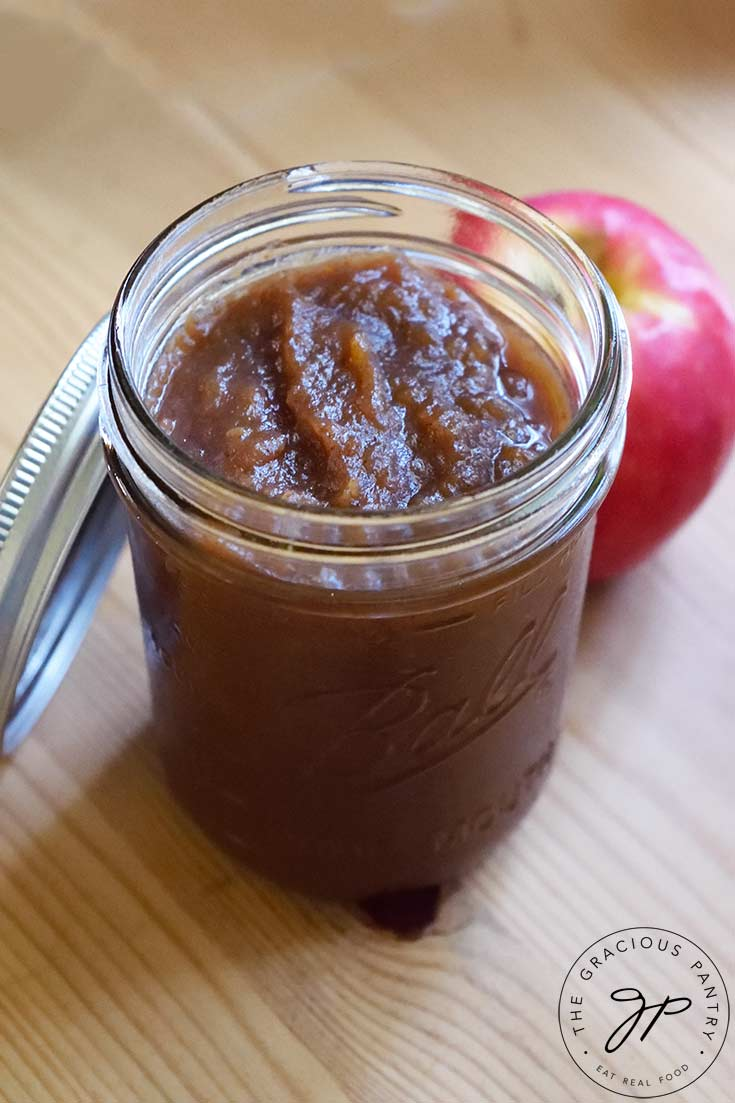 A canning jar filled with this Amish Apple Butter Recipe sits on a wooden surface. The can lid rests on the side of the jar and an apple sits to the back right of the jar.