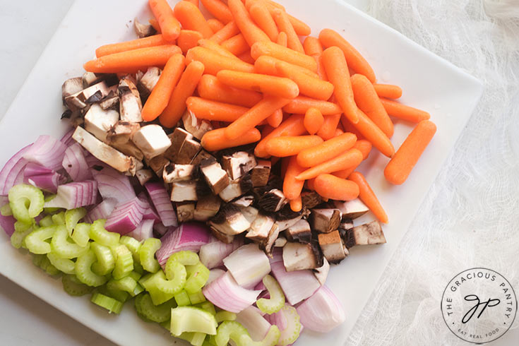 Cut celery, onions mushrooms and baby carrots on a white plate.