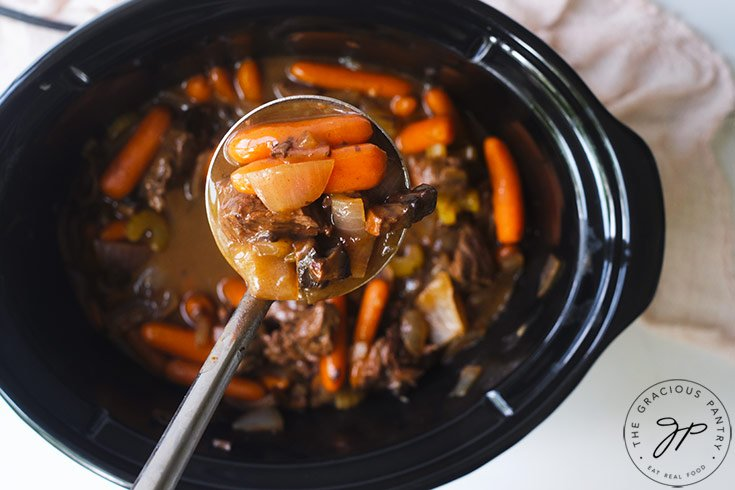 A ladle holding some of the Bison Stew Recipe up to the camera.