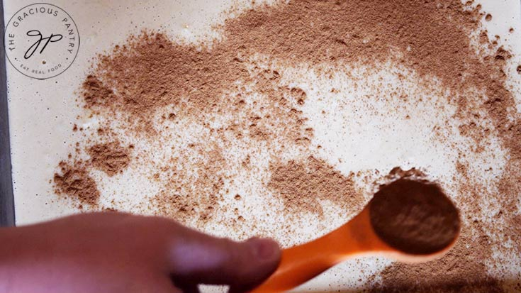 Sprinkling the cinnamon over the wet batter.