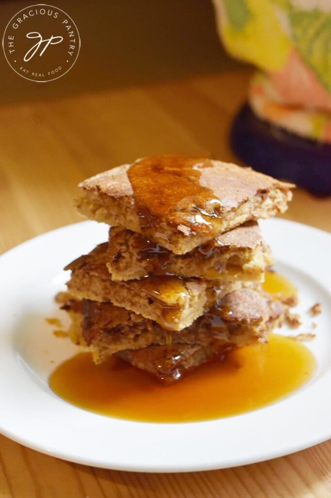 Cinnamon Swirl Pancakes on a white plate sitting on a wooden table.