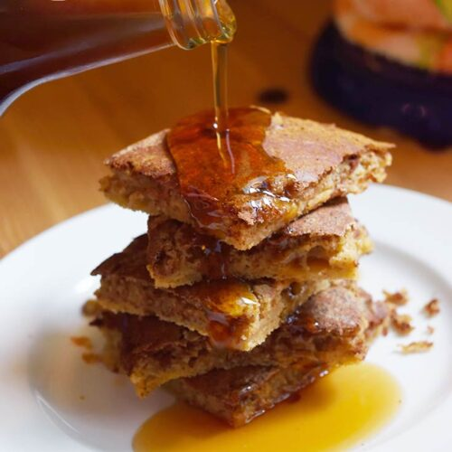 Maple syrup being poured over served Cinnamon Swirl Pancakes.