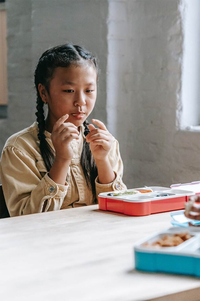 A young girl sits at a lunch table, eating with her lunchbox in front of her.