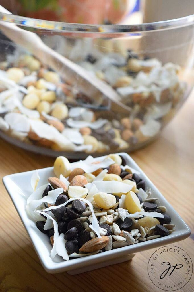 A small, white dish of Low Carb Trail Mix sits in front of a large, clean mixing bowl filled with more Low Carb Trail Mix.