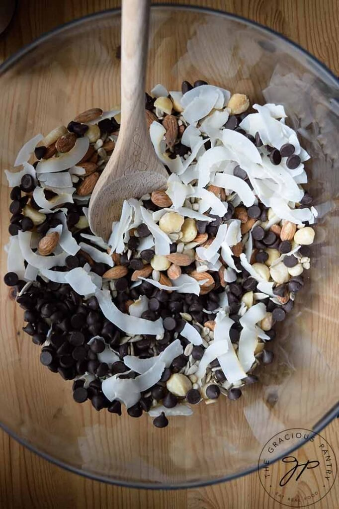 A clean mixing bowl with a wooden spoon resting in it. All the ingredients for this Low Carb Trail Mix Recipe sit in the bowl for mixing.