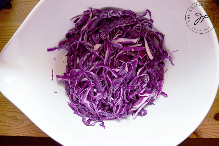 The shredded red cabbage in a large white mixing bowl.