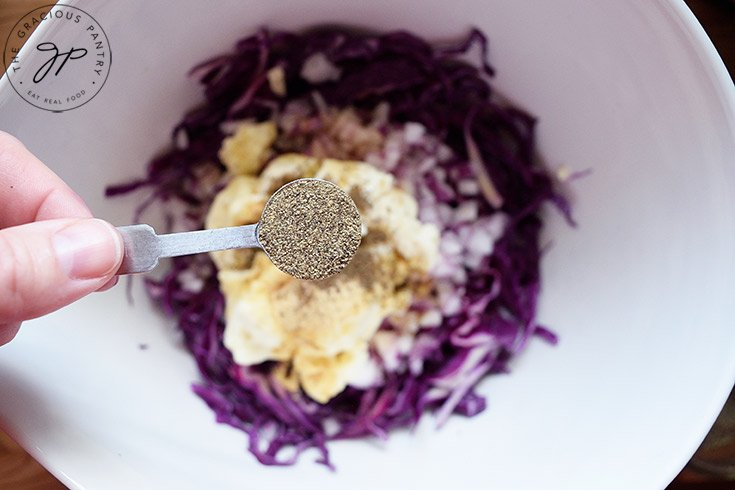 Holding a measuring spoon of black pepper over the mixing bowl to add to this red cabbage slaw recipe.