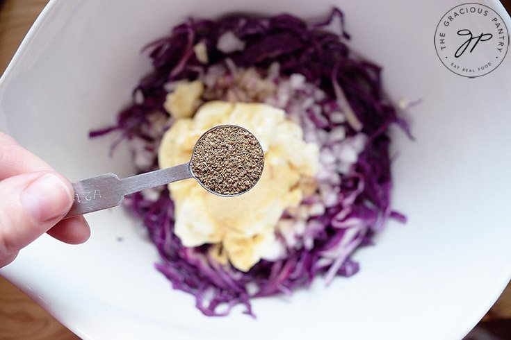 Holding a half teaspoon measure of ground black pepper over the mixing bowl to add to this Red Cabbage Slaw Recipe.