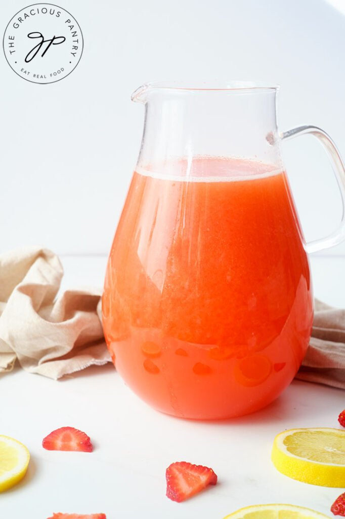 A side view of a clear pitcher filled with Strawberry Lemonade.