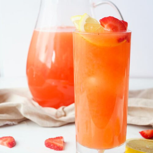 A tall, skinny glass, filled with Strawberry Lemonade and garnished with lemon and strawberry slices.