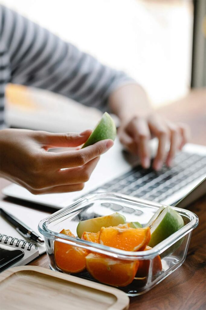 Person at a computer eating fresh apple and orange slices in this guide to Healthy Snacks For Teachers