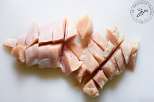 Two chicken breasts, cut into big chunks on a white cutting board.