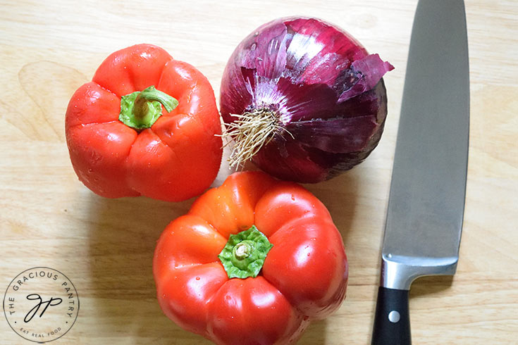 A red onion and two red bell peppers sit next to a knife on a wooden cutting board.