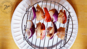 An air fryer skewer rack sits on a white plate. Two kabobs lay on the rack, ready to go into the air fryer.
