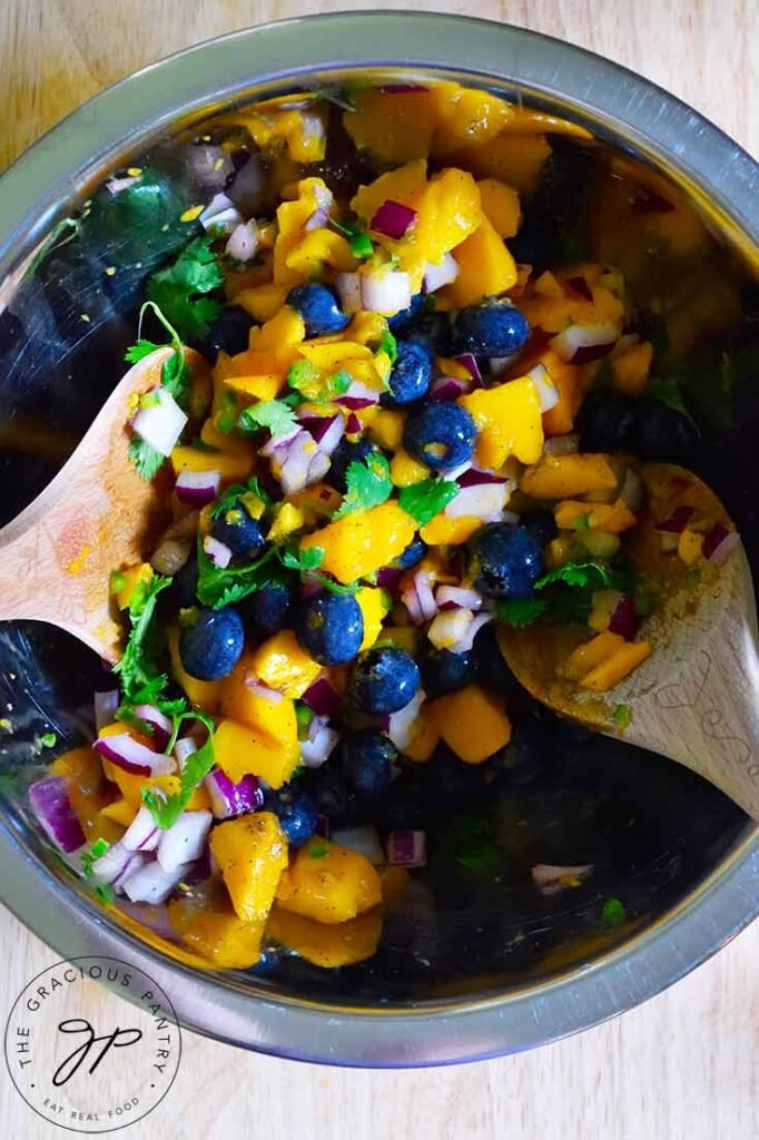 An overhead shot of the Blueberry Mango Salsa being mixed in a stainless steel mixing bowl.