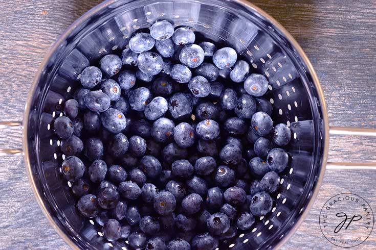 A metal strainer filled with washed blueberries.