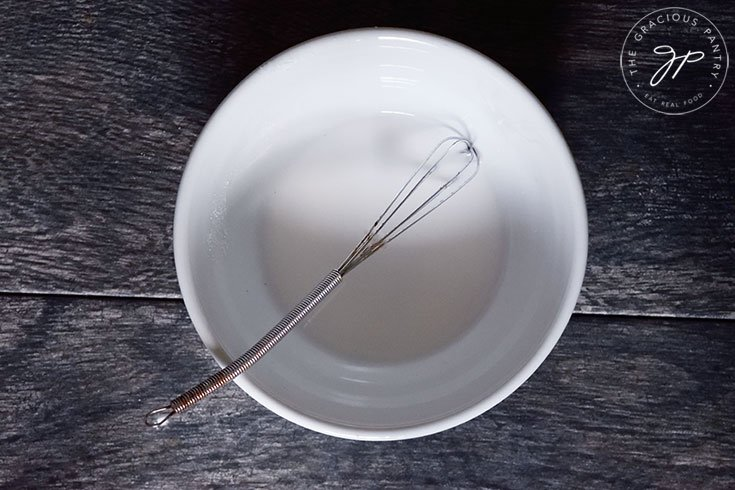 A white bowl sits with a small whisk in a small puddle of slurry.