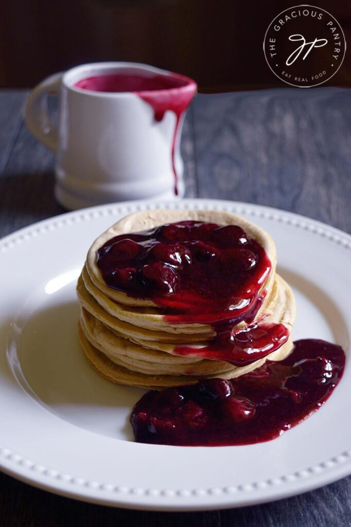 A plate of pancakes with blueberry syrup on a table. A pitcher of Blueberry Syrup sits behind the plate on the table.