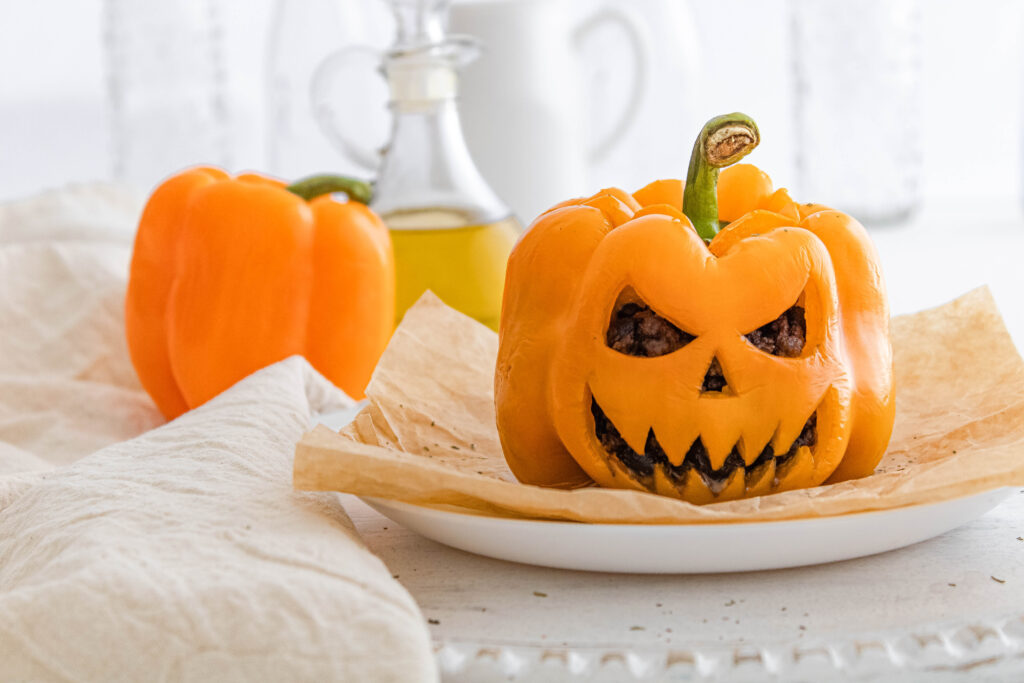 The finished Jack-O-Lantern Stuffed Peppers being served on a white platter.