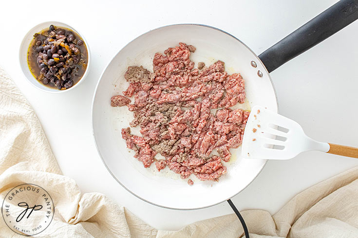 Scrambling the ground meat with a spatula.