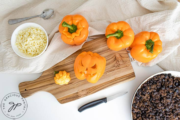 Cutting the Jack-O-Lantern faces into the peppers.