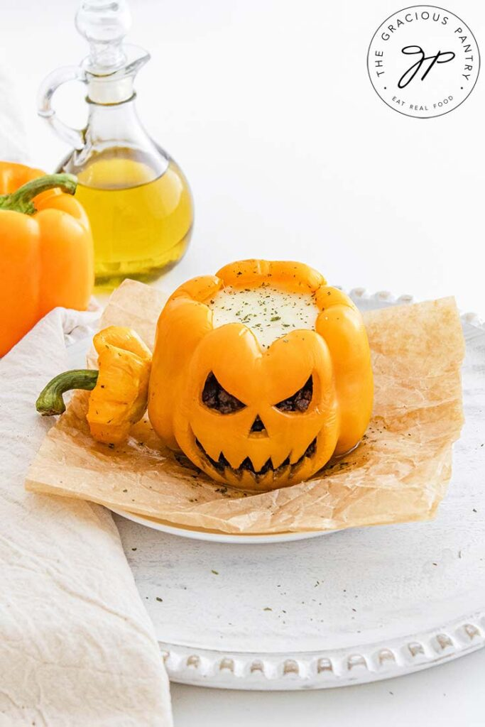 A slightly overhead view of a Jack-O-Lantern Stuffed Pepper on a white platter. A second pepper sits behind it on the table.