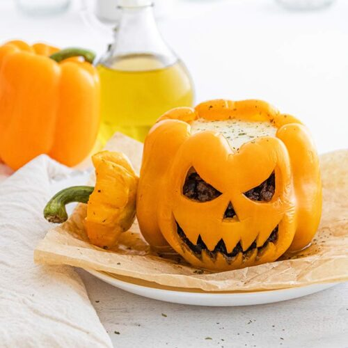 A Jack-O-Lantern Stuffed Pepper sits on a white plate with it's top resting to the side.