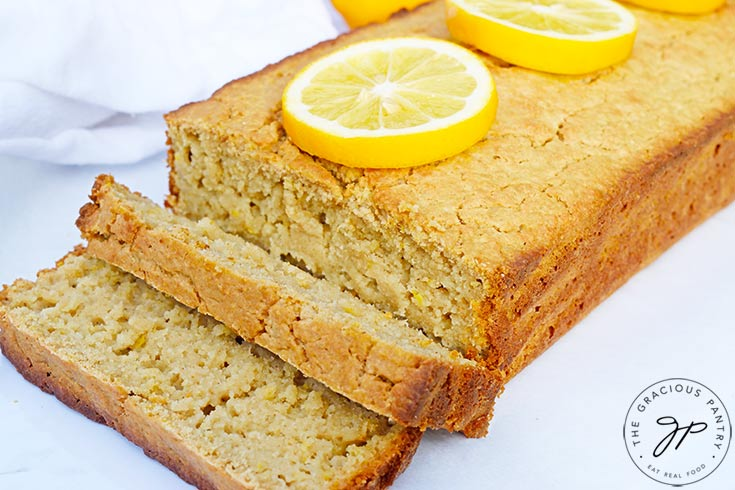 The finished loaf of Lemon Bread on a white background with two slices sliced off and laying at the front of the loaf.