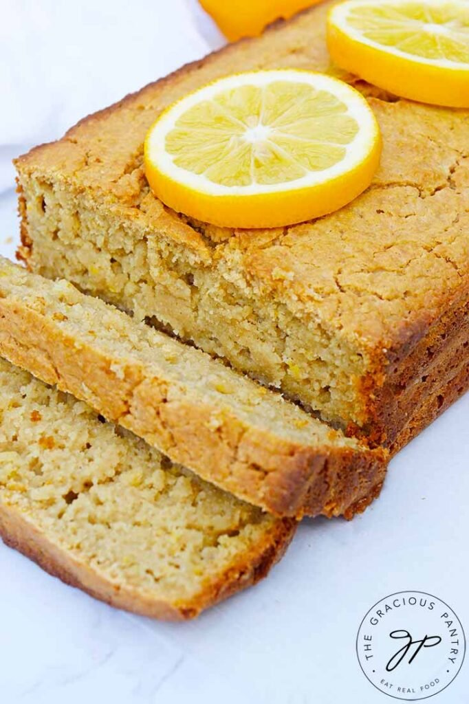 The loaf of Lemon Bread on a white background. Two slices are sliced at the front of the loaf.