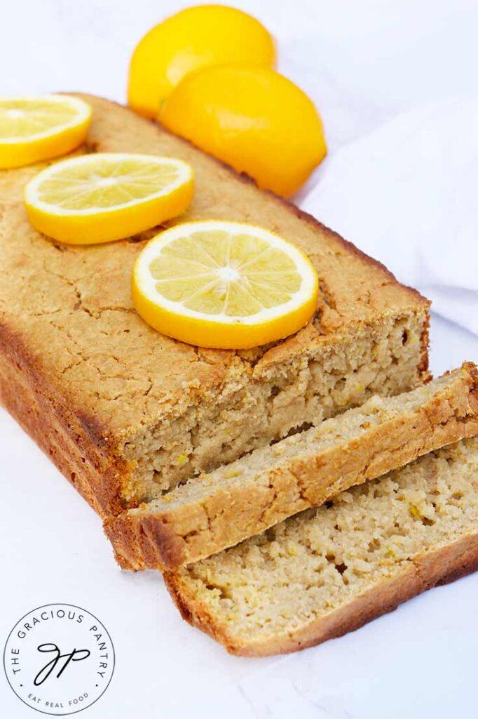 A sliced loaf of lemon bread with lemon slices garnishing the top of the uncut portion.