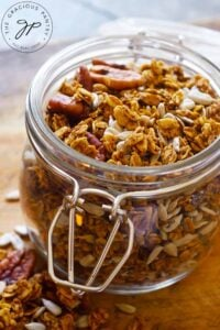 A close up view of an open jar filled with this Pumpkin Granola Recipe.