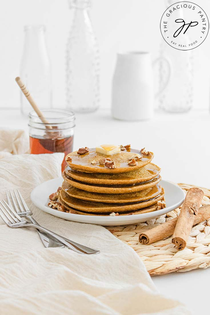 A plate of Pumpkin Oatmeal Pancakes sits on a white table with white jars and glasses sitting behind it.